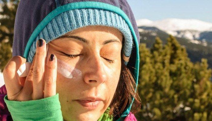 chica aplicando protector solar en invierno