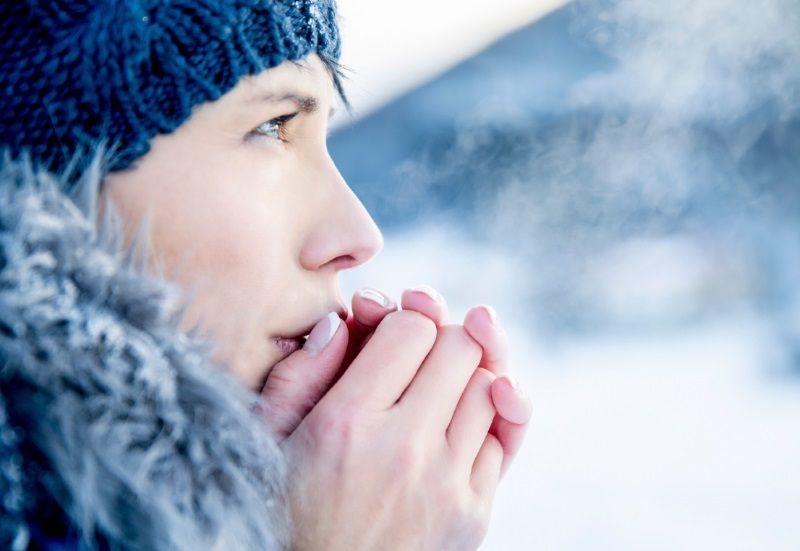 Chica con manos en su boca por el frío