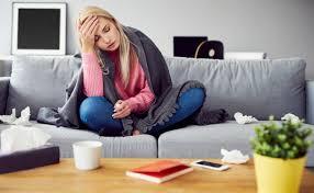 chica en sofa tomandose la temperatura de la frente con una mano