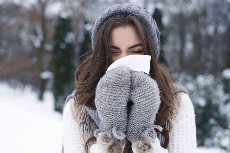 chica con guantes y pañuelo tapandose la cara con fondo invernal
