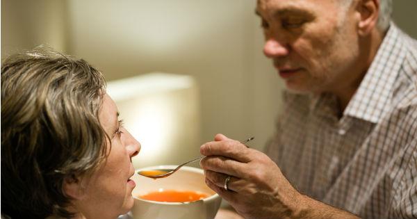 Hombre alimentando a su esposa enferma