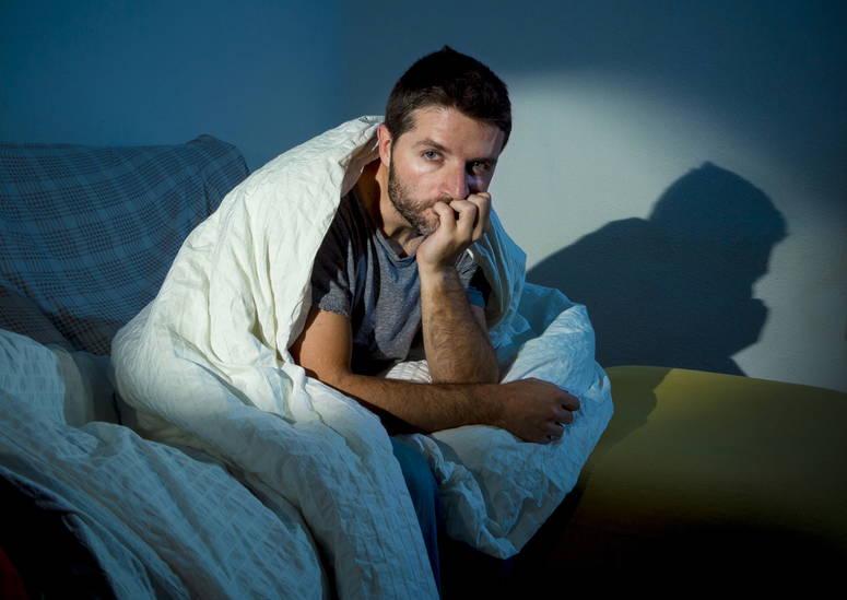 Hombre en cama con insomnio