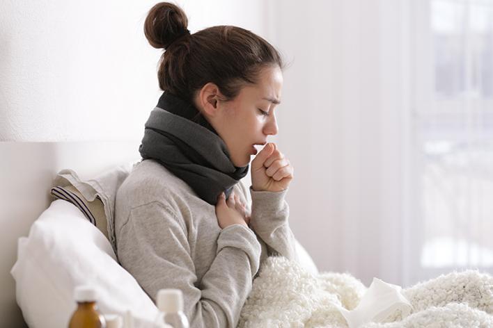 Chica tosiendo en cama