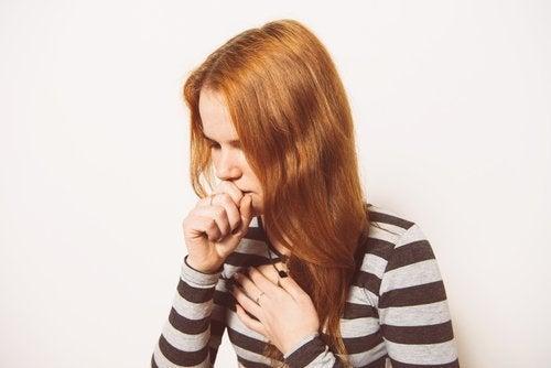 Chica pelirroja tosiendo