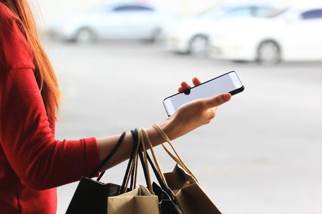 Chica comprando con celular en la mano