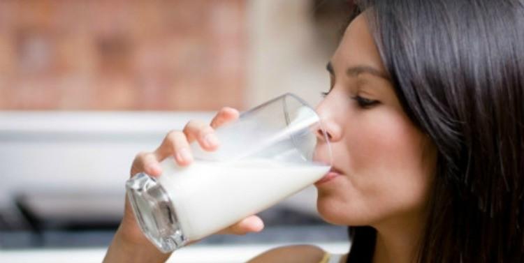 Chica tomando leche en un vaso de vidrio